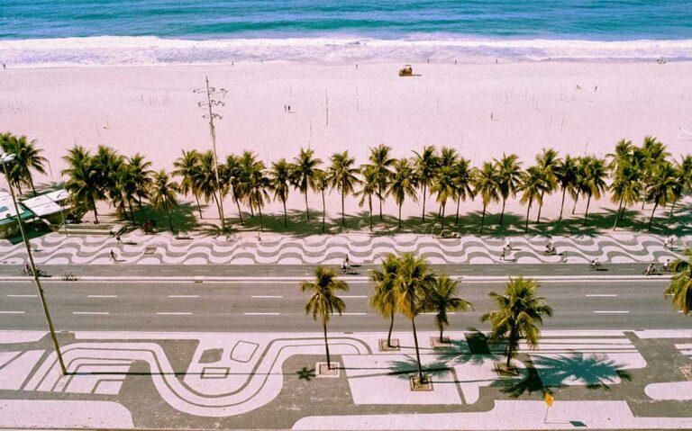 vista aérea de calçada, coqueiros, areia e mar em Copacabana, uma opção de onde ficar no rio de janeiro