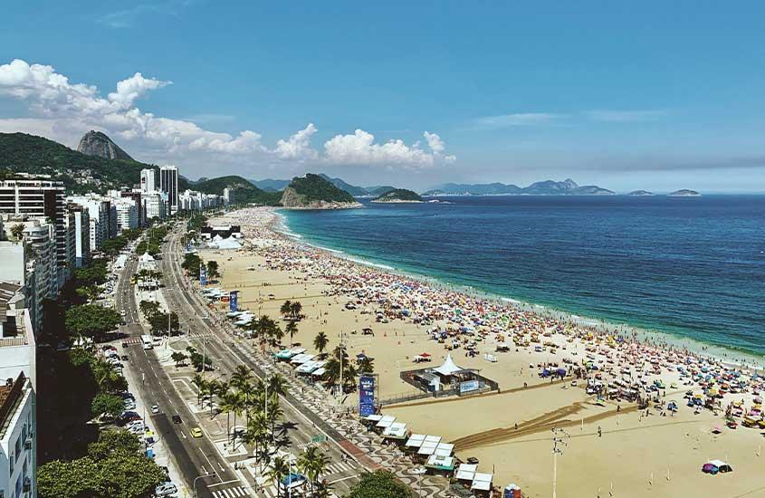 vista aérea de carros em avenida, pessoas em areia e mar durante o dia em Copacabana, uma opção de onde ficar no rio de janeiro