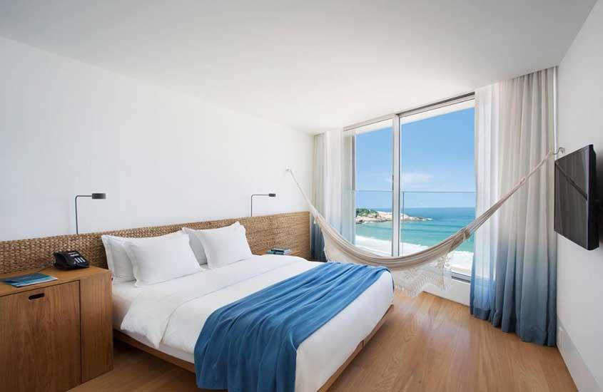 cama de casa, rede de descanso e televisão em quarto com vista para o mar em Hotel Arpoador, uma opção de onde ficar no rio de janeiro
