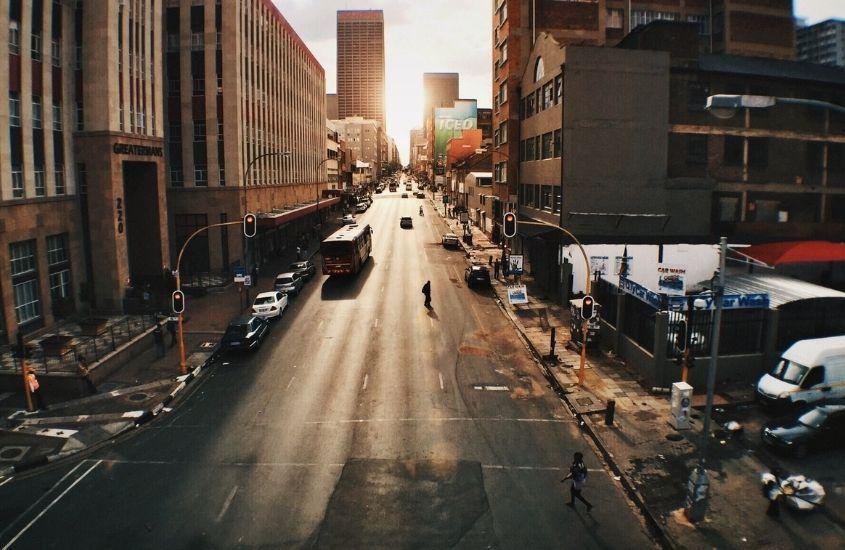 pessoas caminhando em avenida cercada de prédios em Joanesburgo, um dos pontos turísticos da áfrica do sul