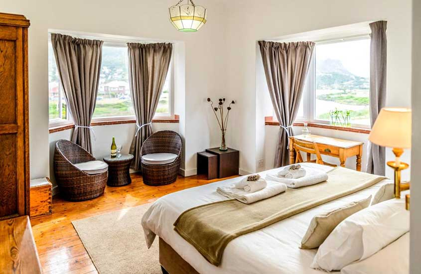 quarto com cama de casal, poltronas e mesa em hotel The Muize
