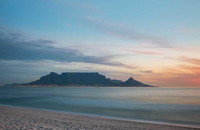 pôr do sol em Bloubergstrand, uma das melhores praias da África do Sul