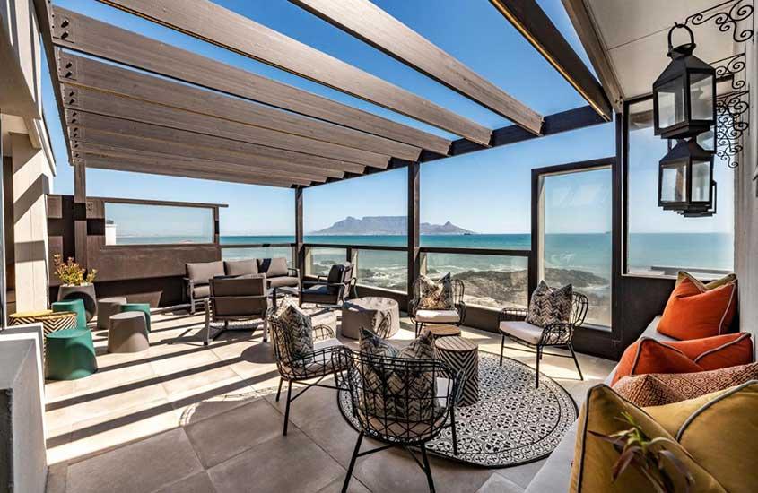 cadeiras, mesas e sofá em varanda de Belle Maroc, um lugar para ficar em Bloubergstrand