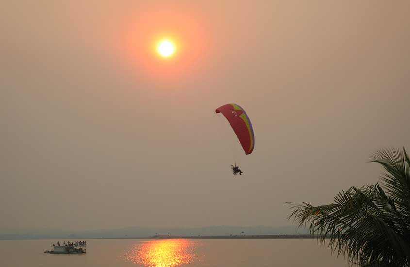 pessoa passando de paraquedas sobre o mar em palmas tocantis