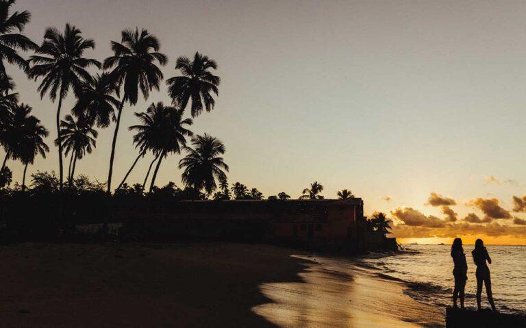 Casal andando na praia durante entardecer