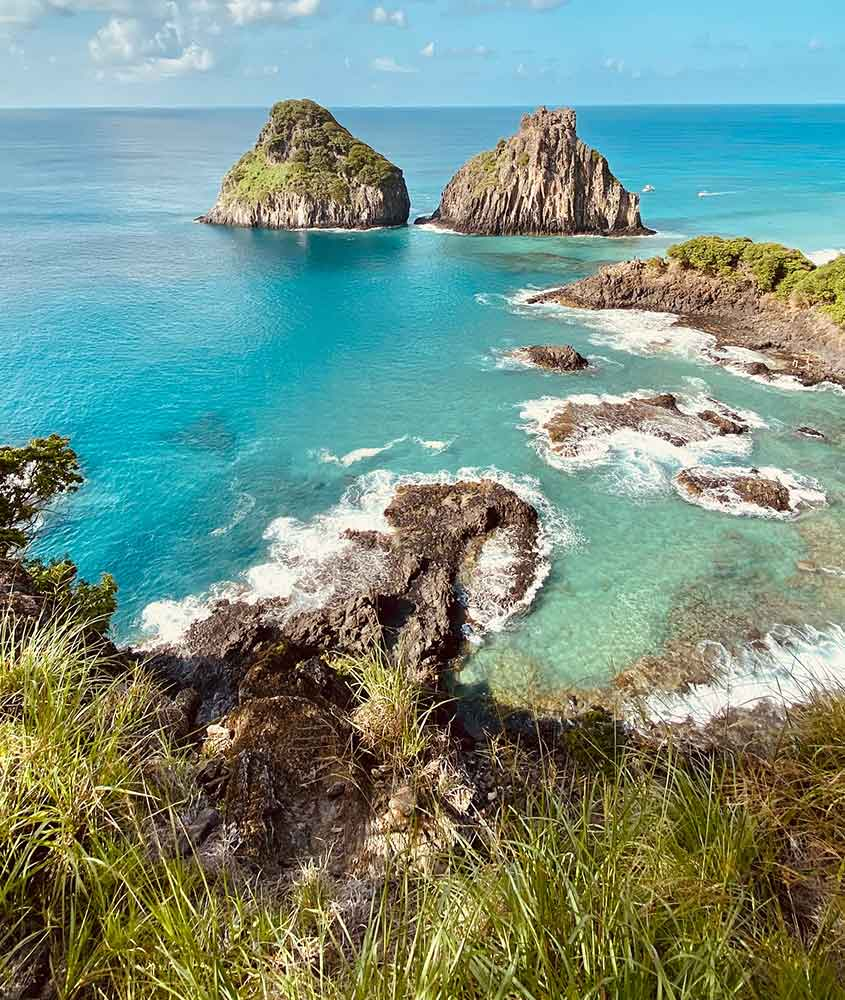 rochas e mar em dia ensolarado em Fernando de Noronha, um ótimo lugar para viagem pelo litoral brasileiro