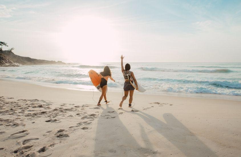 duas mulheres caminham para o mar segurando pranchas de surf