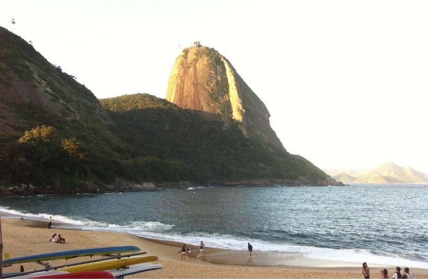 pessoas em areia de Praia Vermelha, onde há a fundo o Morro da Urca, um dos lugares mais bonitos do Rio de Janeiro
