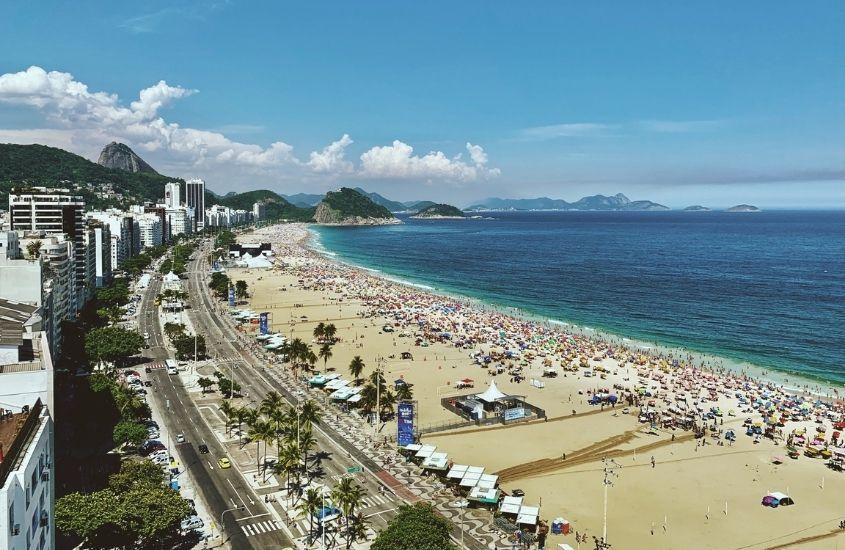 vista aérea de prédios, carros, areia e mar em Copacabana, um dos lugares mais bonitos do Rio de Janeiro