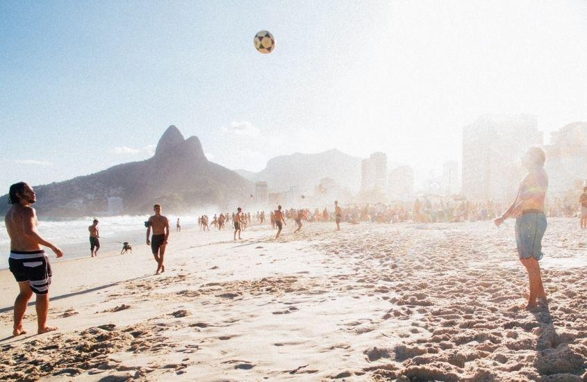 Jovens jogando altinha na praia do Arpoador, uma lugares mais bonitos do Rio de Janeiro
