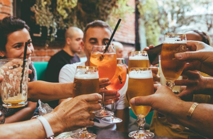 pessoas segurando drinks fazem brinde