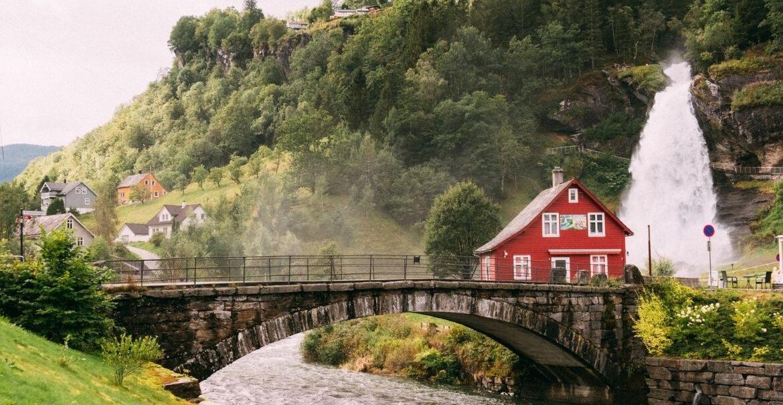 casa vermelha em ponte sobre o rio e em frente a montanha cheia de árvores, durante o dia na europa